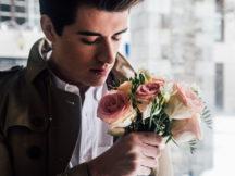 Erstes Date - junger Mann hält zarte Fresien in der Hand